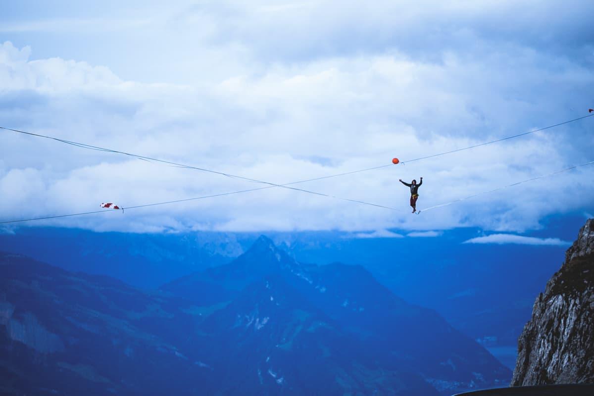 onetotwo slackline profi moritz hamberger auf einer highline vor einem blauen bergpanorama